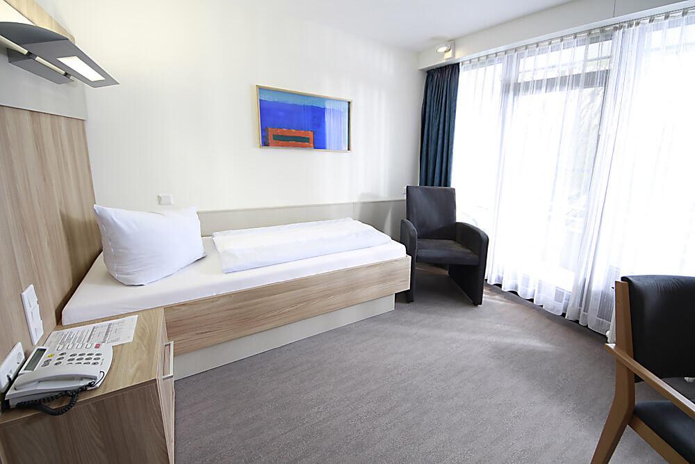 Zimmeransicht mit Bett und Fenstern in der Rehaklinik Eichholz